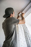 Young man installing curtains over window Stock Image