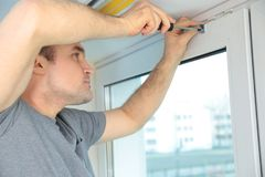 Young man installing window shades. At home royalty free stock photography
