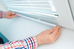Young man installing window shades. At home stock photography
