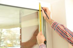 Young man installing window shades. At home royalty free stock image