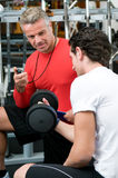 Young man with instructor at gym Royalty Free Stock Photo