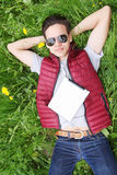 Young man with iPads. Young man lying in the grass with iPads Stock Photography