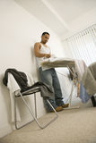 Young Man Ironing Stock Photo