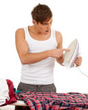 Young man ironing clothes Stock Images