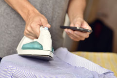 Young man ironing clothes while using a smartphone Royalty Free Stock Image