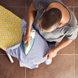 Young man ironing a shirt Stock Photo
