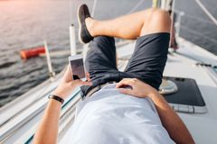 Young Man Is Lying On Yacht Board And Chilling. He Holds Phone In Lefy Hand. Right One Is On Stomach. He Keeps Right Leg Royalty Free Stock Images