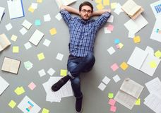 Young man isolated on grey background with papers and notes relaxed looking camera royalty free stock photos