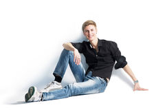 Young man isolated on white background. Smile. Sitting. Stock Photography