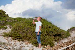 Young man ist drinking water summertime dune beach sky Royalty Free Stock Images