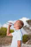 Young man ist drinking water summertime dune beach sky Royalty Free Stock Photography