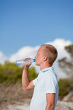 Young man ist drinking water summertime dune beach sky Royalty Free Stock Photo