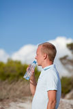 Young man ist drinking water summertime dune sky Stock Image