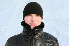 Young man in jacket and cap by winter day. Portrait of young man in jacket and cap by winter day Royalty Free Stock Photos