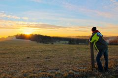 Young man in jacket looking to famous witer sunrise on Czech countryside stock images
