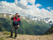 A young man in a jacket stands near the cliff and smiles on the background of the North Caucasus mountain range Stock Photography