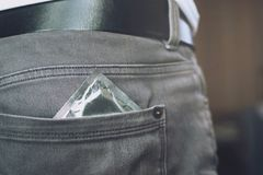 Young man jeans back side pocket to carry condoms taking in hand condom. From jeans, safe sex concept on the bed Prevent infection stock image