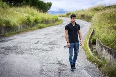 Young man in jeans and black t-shirt walking along Royalty Free Stock Images