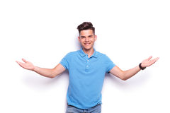 Young man in jeans and blue polo shirt welcoming Stock Photography