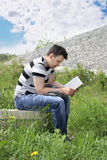 Young man in jeans intently reads book. Outdoor at summer day Stock Images