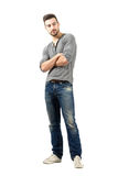 Young man in jeans looking away with crossed arms Stock Photo