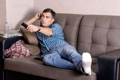 A young man in jeans, with a remote control for the TV boredom on the face changes the channel.  Stock Images