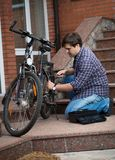 Young man in jeans and shirt repairing bicycle at house backyard. Man in jeans and shirt repairing bicycle at house backyard Royalty Free Stock Photo