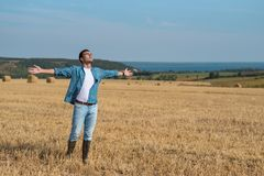 Young man in jeans, shirt, rubber boots in the field with his hands open, the concept of freedom, motivation, movement, front stock images