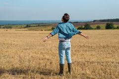 Young man in jeans, shirt, rubber boots in the field with his hands open, the concept of freedom, motivation, movement, portrait royalty free stock photography
