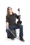 Young man in jeans sits in studio with electric violin Royalty Free Stock Photography