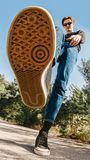 A young man in jeans and sneakers goes on the road among the trees stock images