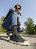 Young man in jeans and sneakers sits on the road in the woods royalty free stock images