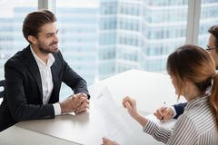 Young man at job interview answering questions of employer. Young men at job interview answering questions of employer. Two HR managers talking with successful stock photo