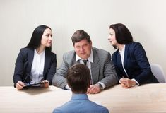 Young man during job interview and members of managemen royalty free stock photography
