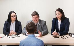 Young man during job interview and members of managemen. Young men during job interview and members of managemen. HR concept Stock Photography