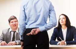 Young man during job interview and members of managemen. Young men during job interview and members of managemen. Young men with fingers crossed behind back stock image
