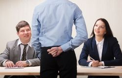 Young man during job interview and members of managemen. Young men during job interview and members of managemen. Young men with fig sign behind back concept Royalty Free Stock Images