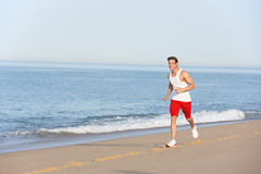 Young Man Jogging Along Beach Royalty Free Stock Photography
