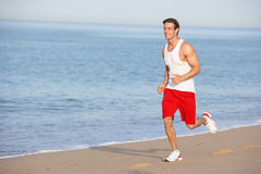 Young Man Jogging Along Beach Royalty Free Stock Images