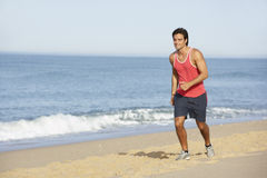 Young Man Jogging Along Beach Stock Photography