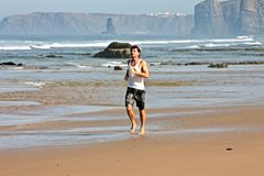 Young man jogging along the beach at the atlantic Royalty Free Stock Images