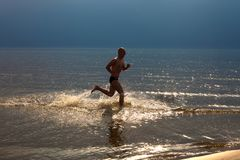 Young man jogging along the coast line royalty free stock photography