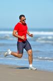 Young man jogging on the beach Royalty Free Stock Photography