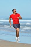 Young man jogging on the beach. In summer Stock Photography