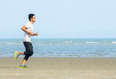 Young man jogging on the beach. In summer Royalty Free Stock Images
