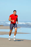 Young man jogging on the beach in summer Royalty Free Stock Image