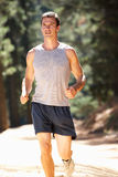 Young man jogging through the countryside. Smiling Stock Image