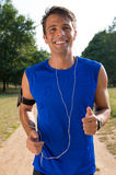 Young Man Jogging While Listening Music. Portrait Of A Young Man Listening To Music On Headphone While Jogging royalty free stock photography