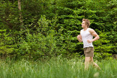 Young man jogging in nature. In sportive outfit Stock Photography