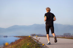 Young man jogging near the lake Royalty Free Stock Images